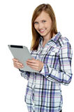 Attractive cute girl holding a tablet device Stock Images