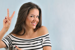 Attractive cute happy young woman enjoying life with peace gestu Royalty Free Stock Image