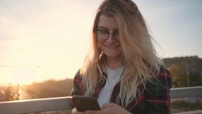 Pretty teenager girl is using her smartphone at sunset. Attractive and cute millennial teenager in hipster outfit smiles and laughs while uses her smartphone for stock video