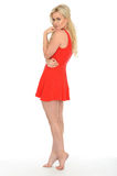 Attractive Cute Sexy Young Blonde Woman Wearing a Short Red Mini Dress. Attractive cute Sexy Young Blonde Haired Woman in Her Twenties, side on to camera Royalty Free Stock Photo