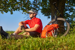 Attractive cyclist in the helmet sitting on the green meadow near the cycle in the countryside. Stock Image