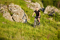 Attractive cyclist riding bike on the meadow with stones in the countryside. Attractive cyclist riding bike on the green meadow with stones in the countryside Stock Photos