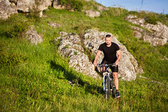 Attractive cyclist riding the bike on summer trail near beautiful big rocks. Stock Image