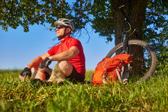 The attractive cyclist sitting on the grass near the bike and near the tree. Sportsman in the red t-shirt, black shorts, sportive shoes, with helmet and Royalty Free Stock Photos
