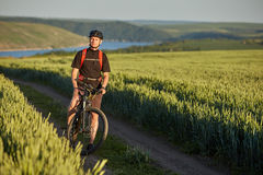 Attractive cyclist stands on the bike on the trail of the hay field in summer season. Royalty Free Stock Photo