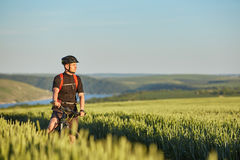 Attractive cyclist stands on the bike on the trail of the hay field in summer season. Young sportsman dressed in the black sportwear, with helmet and backpack Stock Photo