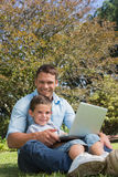 Attractive dad and son smiling in a park Royalty Free Stock Photography