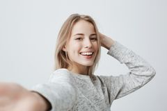 Attractive dark-eyed blonde female dressed casually having delightful look smiling broadly. Beautiful woman having. Horizontal portrait of attractive dark-eyed royalty free stock photos