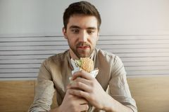 Attractive dark haired guy sitting in cafe, looking with happy expression at sandwich, being happy to eat something Stock Photography