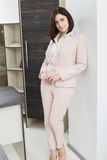 Attractive dark-haired woman dressed in a beige suit standing near the table in the office. Stock Photography