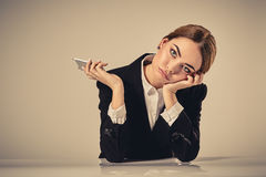 Attractive dark-haired woman dressed in a black suit is sitting Royalty Free Stock Image