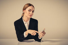 Attractive dark-haired woman dressed in a black suit is sitting Royalty Free Stock Photography