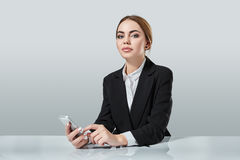 Attractive dark-haired woman dressed in a black suit is sitting at  table in an office. Stock Image