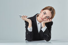 Attractive dark-haired woman dressed in a black suit is sitting at  table in an office. Stock Images
