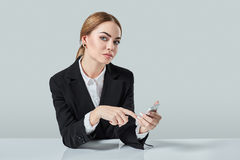 Attractive dark-haired woman dressed in a black suit is sitting at  table in an office. Royalty Free Stock Image