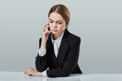 Attractive dark-haired woman dressed in a black suit is sitting at  table in an office. Royalty Free Stock Photos