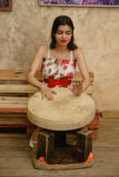 An attractive dark-haired woman is playing a tambourine. A young dark-haired woman in bright clothes is playing a tambourine Royalty Free Stock Photos