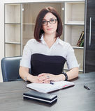 Attractive dark-haired woman in sunglasses sitting in the office of the table. Stock Photos