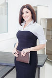 Attractive dark-haired woman wearing a black and white dress standing near the table in the office with notebook. Attractive dark-haired woman wearing a black Stock Photos