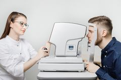 Attractive dark-haired young woman doctor measures eye pressure on ophthalmic equipment to fashionable guy. Attractive dark-haired young women doctor measures royalty free stock image