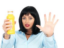 Attractive Dark Haired Young Woman Holding up a Bottle of Fresh Orange Juice. Attractive dark haired Young Woman in her twenties, holding up a bottle of fresh Royalty Free Stock Images