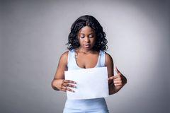An attractive dark-skinned girl in a blue T-shirt on a gray background points the index finger at the white area stock photos