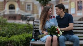 Attractive dating couple sitting on bench in park stock video footage
