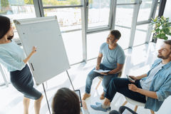 Attractive delighted men visiting a business seminar. Useful training. Attractive nice delighted men sitting around the whiteboard and taking notes while Royalty Free Stock Images