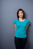 Attractive demure young Asian woman. Standing with her hands behind her back against a dark studio background with copyspace smiling at the camera Stock Photos