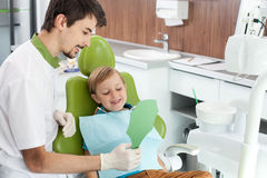 Attractive dental doctor is treating small patient. Cheerful young dentist is standing near child and showing a mirror to him. The child is sitting in chair and Royalty Free Stock Photography