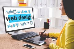 Attractive designer drawing a web design sketch. Side view of a young woman in a yellow shirt drawing a stylish web design sketch on her desktop computer stock images
