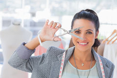 Attractive designer holding scissors in front of her face Royalty Free Stock Images