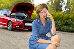 Attractive desperate and confused woman stranded on roadside with broken car engine failure crash accident calling on mobile phone stock images