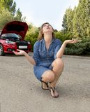 Attractive desperate and confused woman stranded on roadside with broken car engine failure crash accident calling on mobile phone. Young attractive desperate Royalty Free Stock Photo