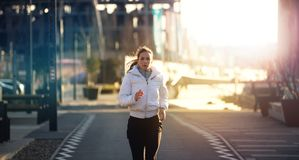 An attractive, determined female running outdoor. stock photography