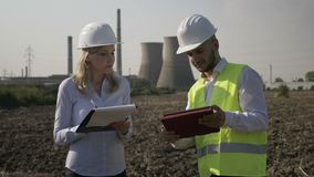 Woman with helmet noting in her notebook working progress report of young engineer using tablet pc near refinery platform -. Attractive developer business woman stock footage