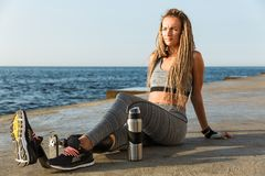 Attractive disabled athlete woman with prosthetic leg. Sitting at the beach with water bottle royalty free stock photography