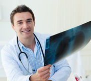 Attractive doctor examining an x-ray. And smiling at the camera Royalty Free Stock Photos
