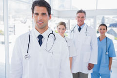 Attractive doctor in front of his team Stock Images