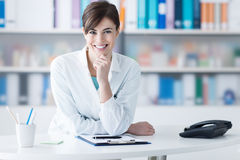 Attractive doctor posing at the clinic reception. Attractive young female doctor leaning on the clinic reception desk with hand on chin, she is smiling at camera Stock Images