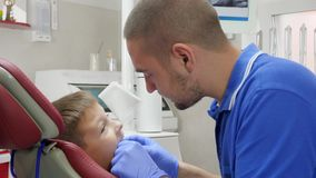 Attractive doctor puts orthodontics plate on teeth to small patient on background of modern apparatus in dentist`s. Attractive doctor into rubber gloves puts stock video