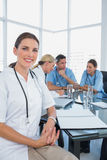 Attractive doctor sitting in front of her team Stock Image