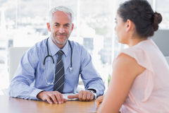 Attractive doctor sitting in front of patient Royalty Free Stock Photo