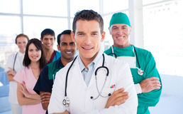 Attractive doctor standing with his colleagues Stock Photos