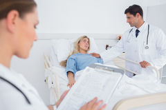 Attractive doctor taking care of a patient. Attractive doctor taking care of a hospitalized patient Stock Image