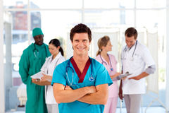 Attractive doctor with is team in the background Stock Images