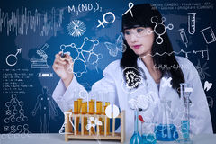 Attractive doctor writing formula on blue Royalty Free Stock Images