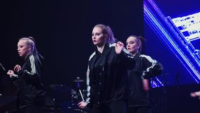 Attractive dynamic girls in black sportive clothes perform on stage at festival. Group of dynamic attractive girls wearing black sport clothes synchronically and stock footage