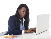 Attractive and efficient black ethnicity woman sitting at office computer laptop desk typing Stock Images