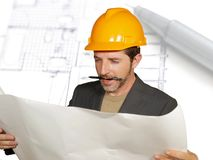 Attractive efficient and confident architect man in builder helmet checking building construction blueprints  on design. Background in architecture development royalty free stock image